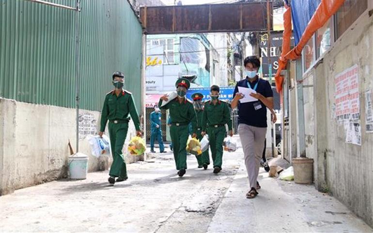 Các chiến sĩ Trung đoàn 88, Sư đoàn 302 (Quân Khu 7) chuyển lượng thực, thực phẩm tặng người lao động nghèo ở hẻm 139 Nguyễn Tiểu La, Quận 10. Ảnh: TTXVN